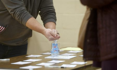 voter using hand sanitizer