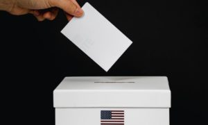 photo of person dropping a vote